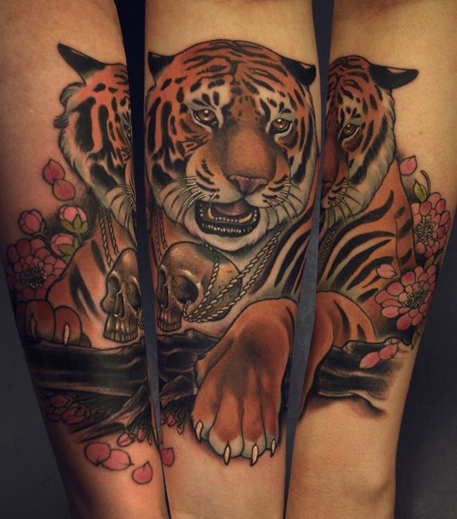 Modern traditional style colored arm tattoo of detailed tiger with flowers and skull