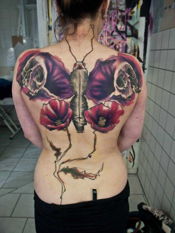 Modern traditional style colored butterfly shaped tattoo on back with human skulls and flowers