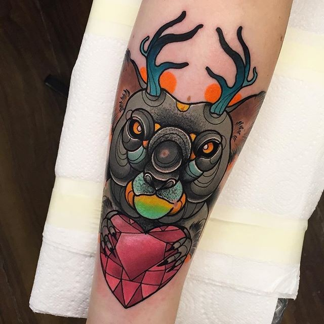 Modern traditional style colored forearm tattoo of mystical bear with deer horns