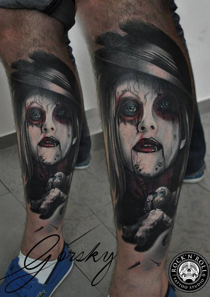 Modern traditional style colored leg tattoo of terrifying woman portrait with voodoo doll