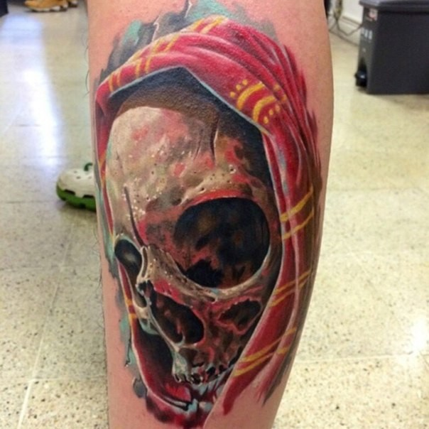Modern traditional style colored leg tattoo of human skull with hood