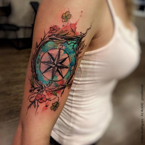Modern traditional style colored shoulder tattoo of compass with flowers