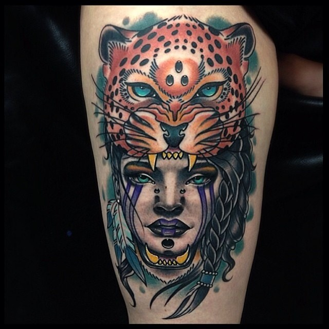 Modern traditional style colored thigh tattoo of woman head with leopard helmet