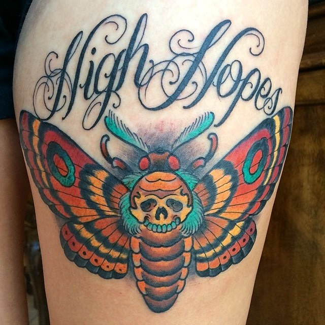 Modern traditional style colored thigh tattoo of big butterfly stylized with human skull and lettering