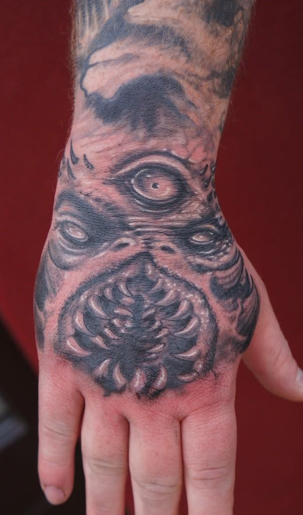 Tatuaggio mostruoso sul braccio la faccia del mostro