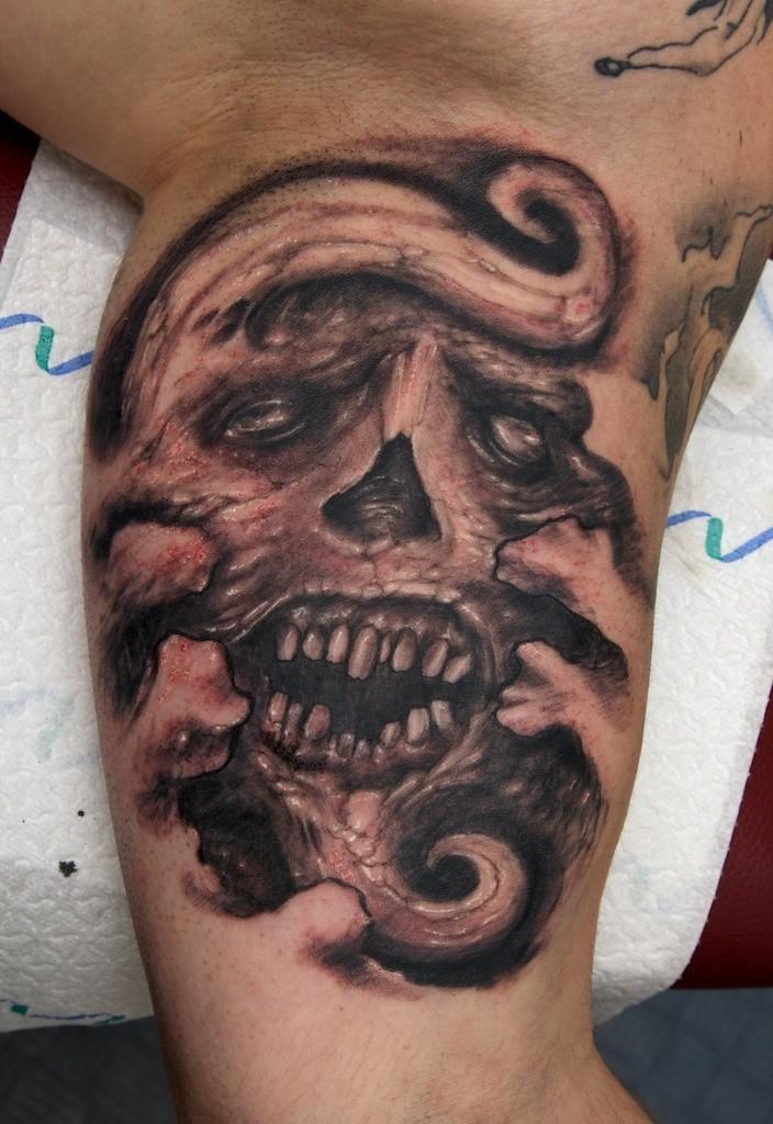 Tatuaje en la pierna, cráneo negro con la boca abierta