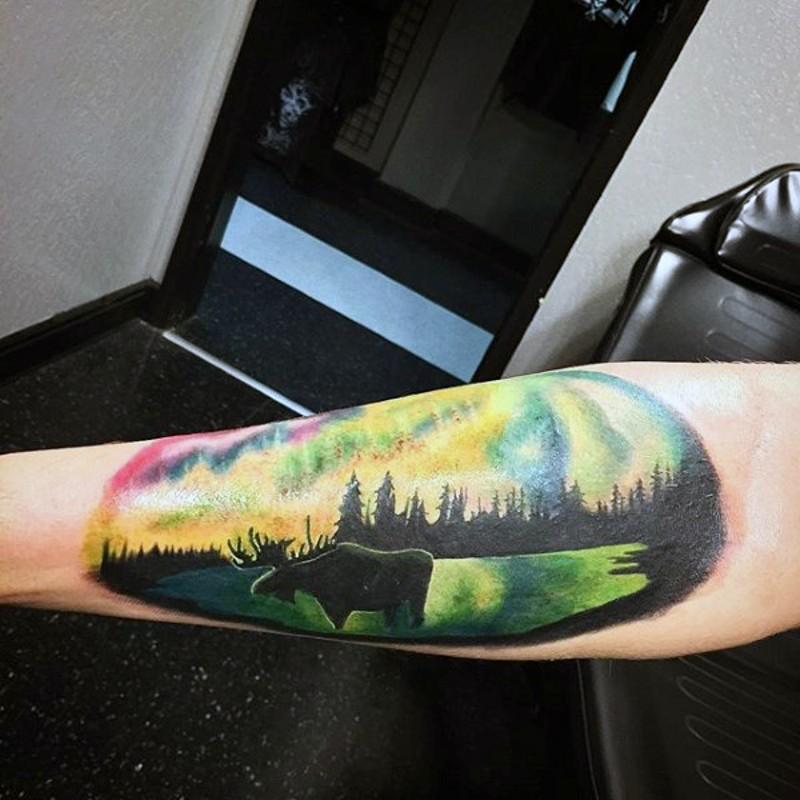 Multicolored elk on wildlife scenery oval shaped arm tattoo