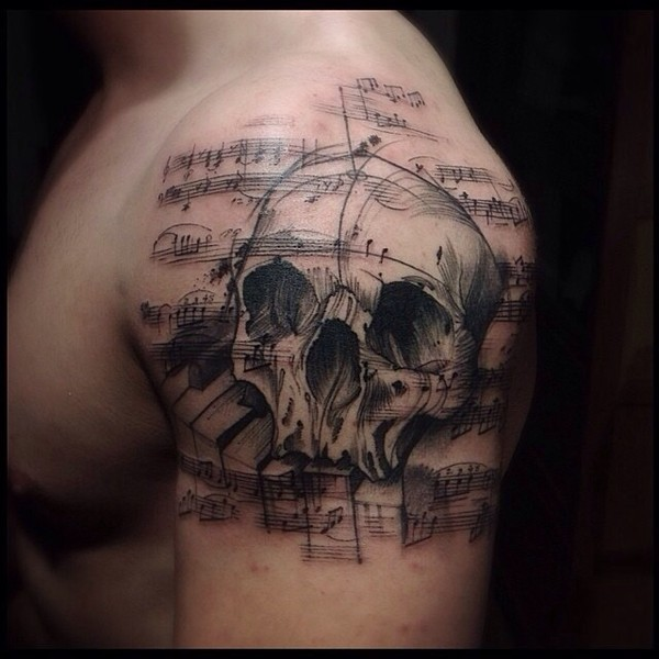 Music themed black ink shoulder tattoo of human skull with notes