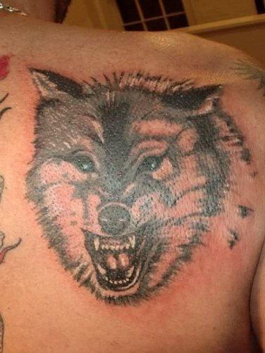 Tatuaje en el hombro, lobo con la boca abierta