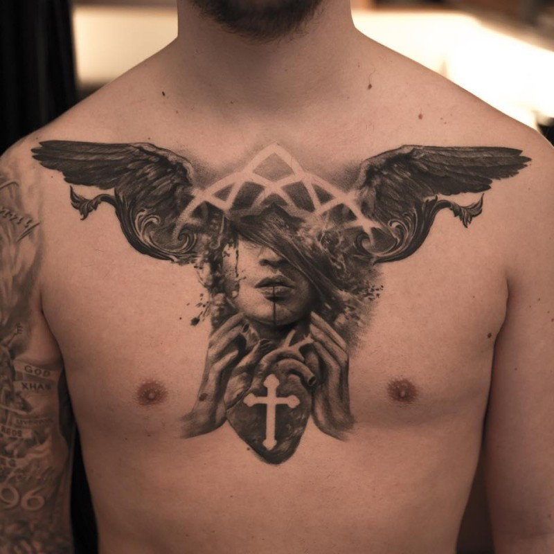 Mysterious black ink chest tattoo of woman face with human heart and wings