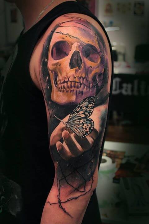 Mysterious designed colored half sleeve tattoo of human skull with hand holding butterfly
