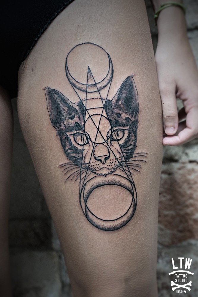 Mysterious style black ink thigh tattoo of cat head with mystical ornaments