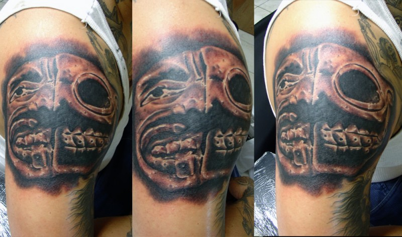 Mystic colored shoulder tattoo of creepy looking face