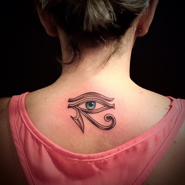 Mystical ancient Egyptian symbol the Eye of Horus tattoo on lady&quots upper back
