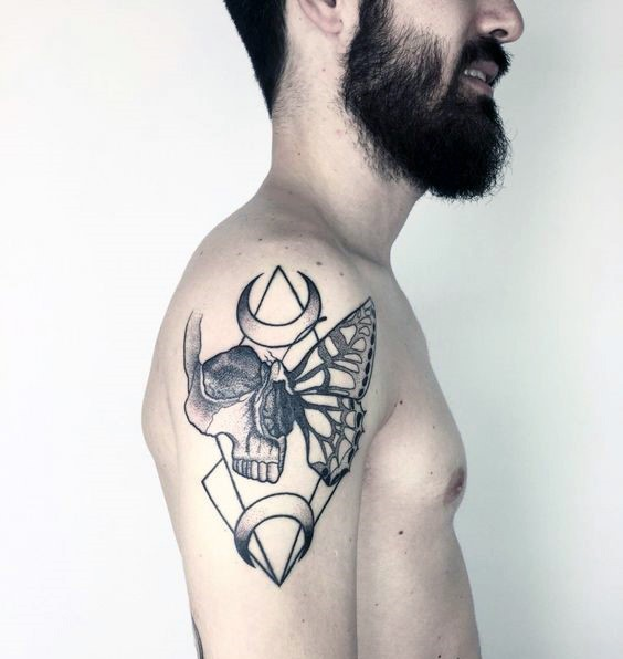 Mystical black ink shoulder tattoo of human skull stylized with butterfly wing and moons