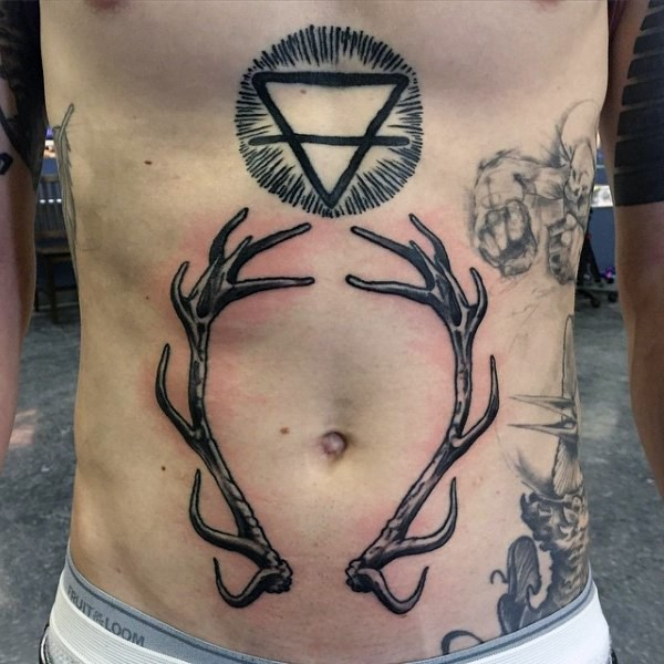 Mystical blackwork style belly tattoo of cult triangle symbol and deer horns