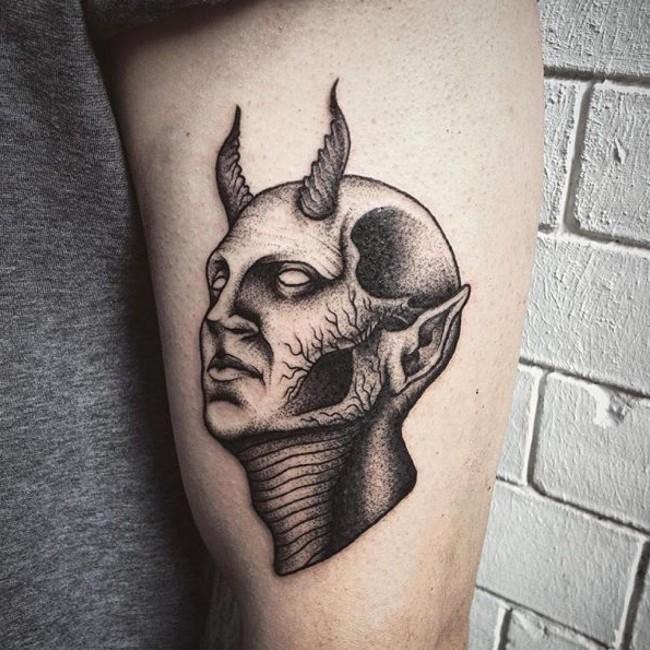 Mystical engraving style black ink biceps tattoo of devil head
