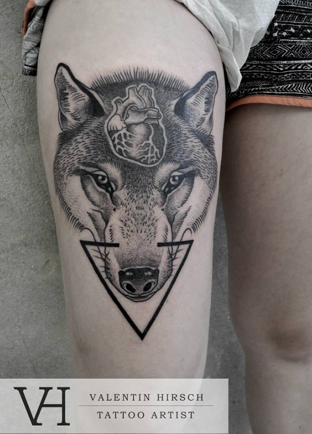 Mystical Engraving style wolf head tattoo on thigh stylized with human hear and black triangle