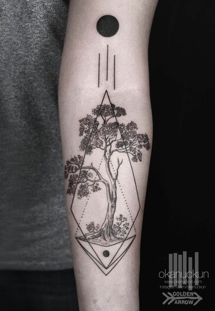 Mystical geometrical style painted tattoo with lonely tree on arm