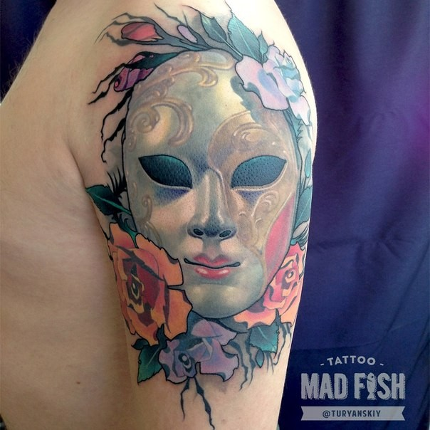 Mystical illustrative style colored shoulder tattoo of mystical mask with flowers