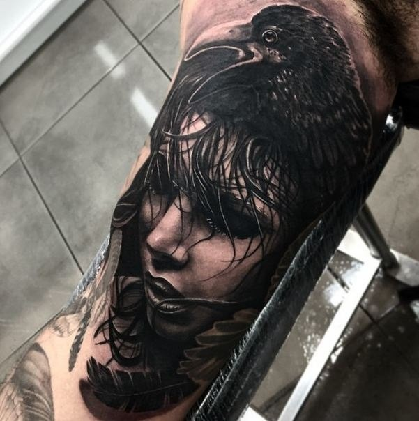 Mystical looking black ink biceps tattoo of sad woman face with crow