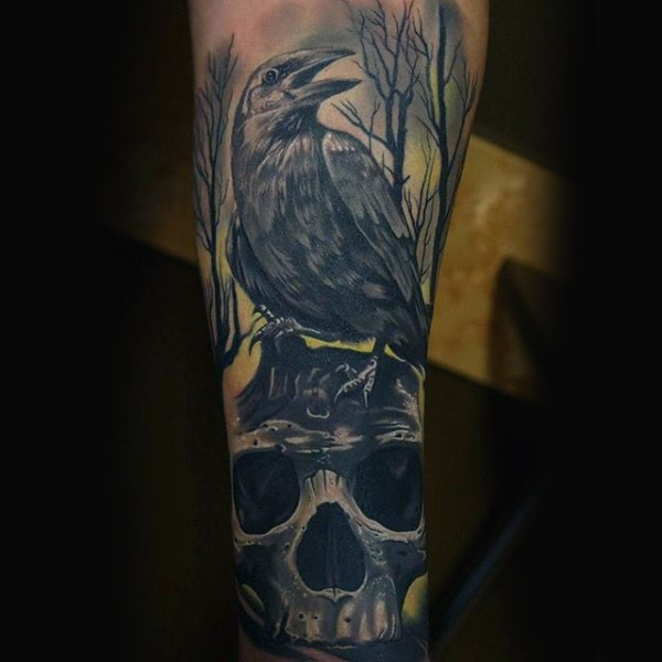 Mystical looking colored arm tattoo of big crow with human skull and dark forest