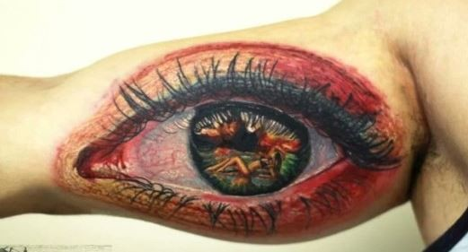 Naked girl in pupil of eye tattoo on arm