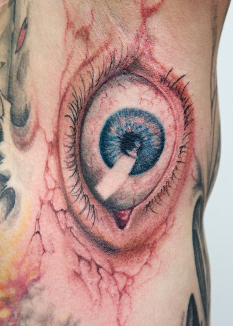 Natural colored horrifying big eye tattoo on side