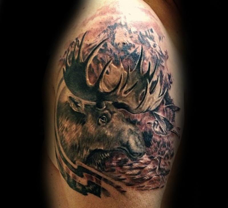 Natural detailed and colroed elk tattoo on shoulder with birds and mountains