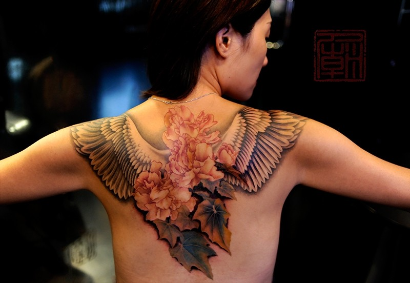 Natural detailed colored flowers tattoo on upper back with bird wings