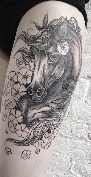 Natural looking big colored sad horse tattoo on thigh stylized with beautiful flowers