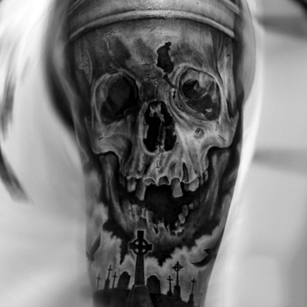Natural looking black and white corrupted human skull tattoo on shoulder combined with dark cemetery