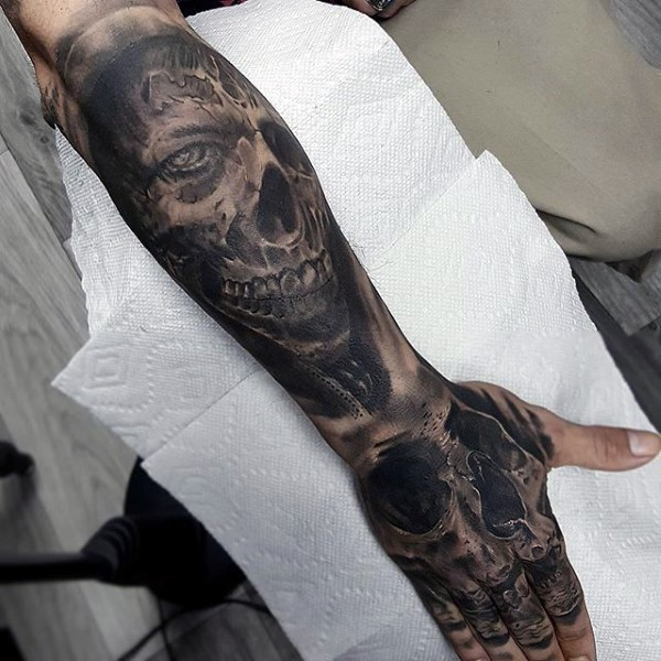 Natural looking black and white forearm tattoo of monster skull combined with human skull