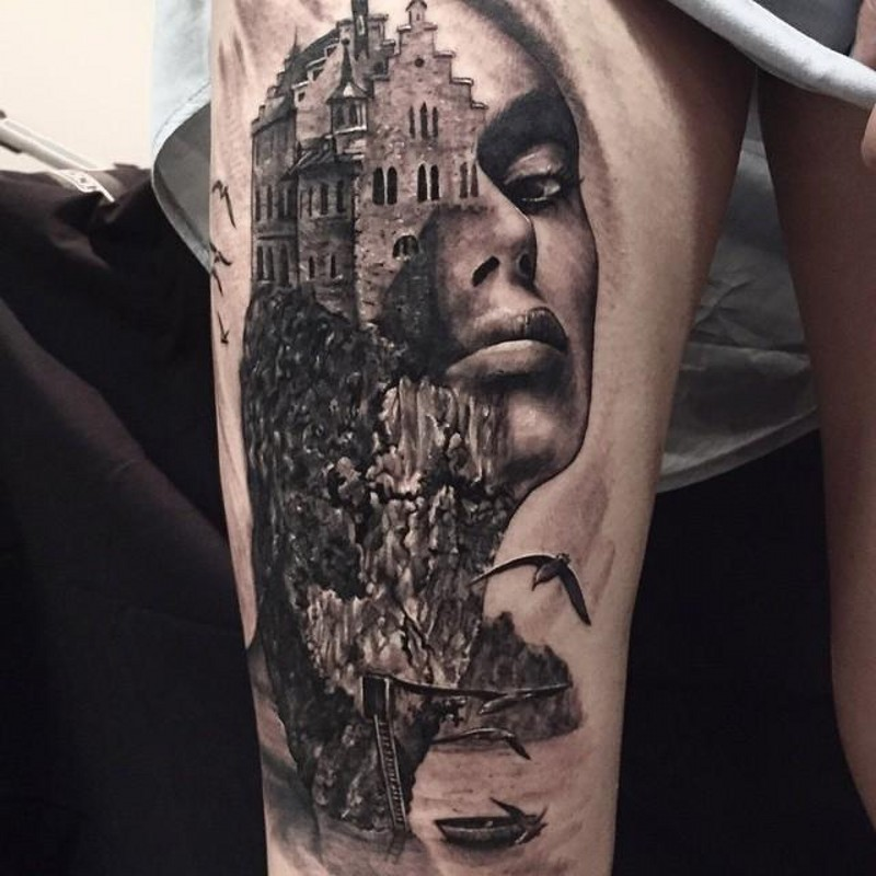 Natural looking black and white thigh tattoo of castle on rock with woman portrait
