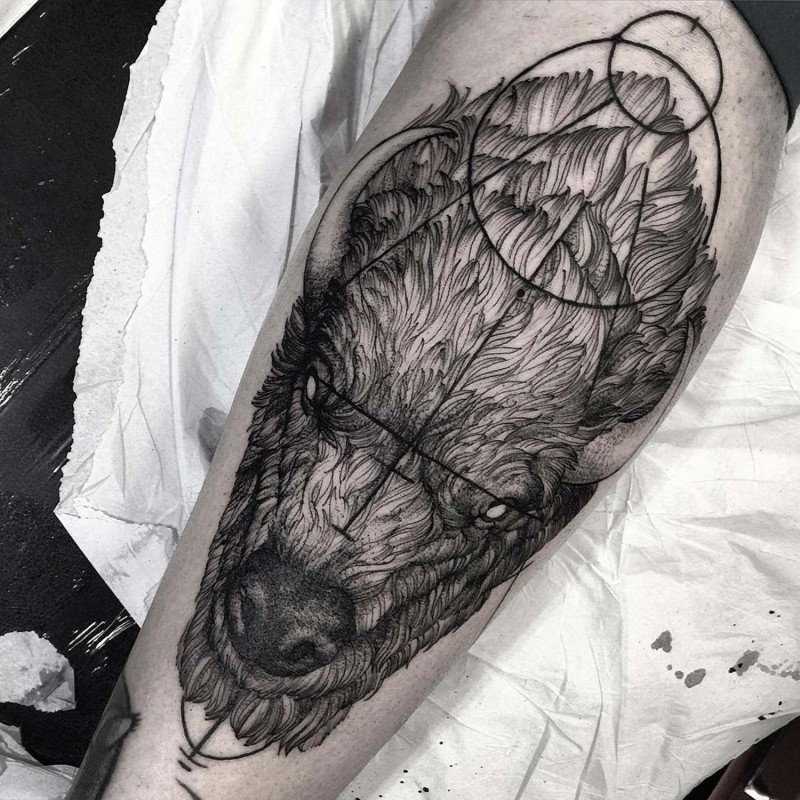 Natural looking black ink bison head tattoo on leg combined with mystical ornaments