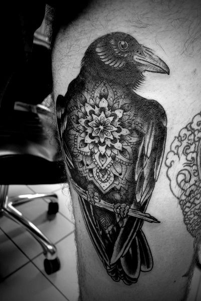 Natural looking black ink crow tattoo on thigh stylized with beautiful flower