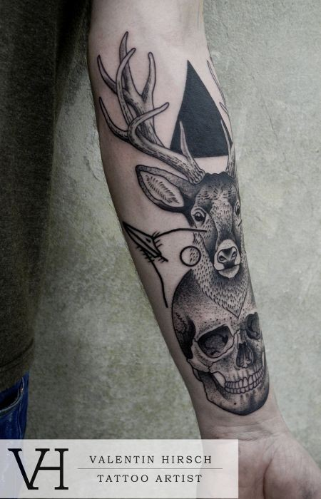 Natural looking black ink deer tattoo on forearm with human skull and black triangle