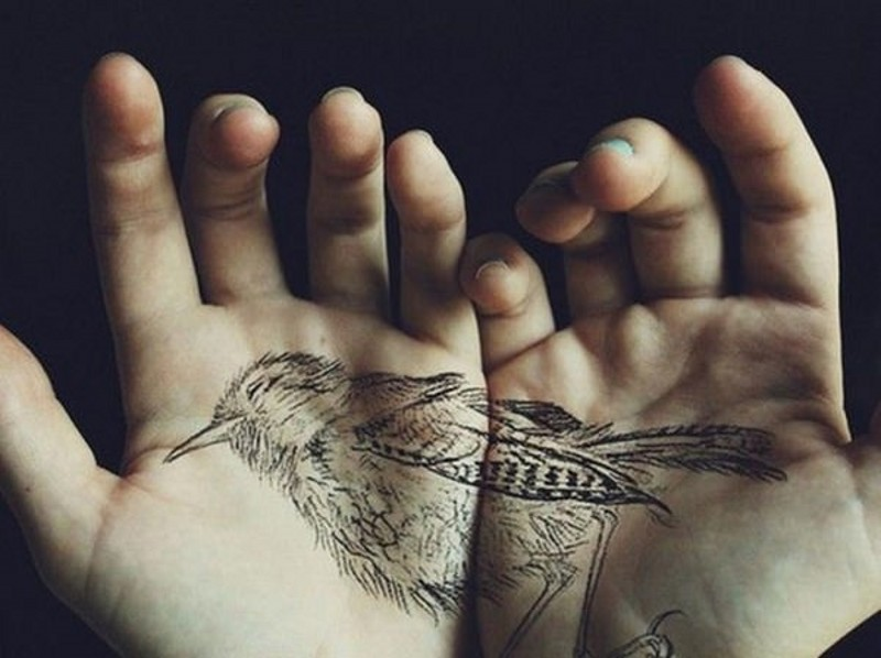 Natural looking black ink detailed divided bird tattoo on hands