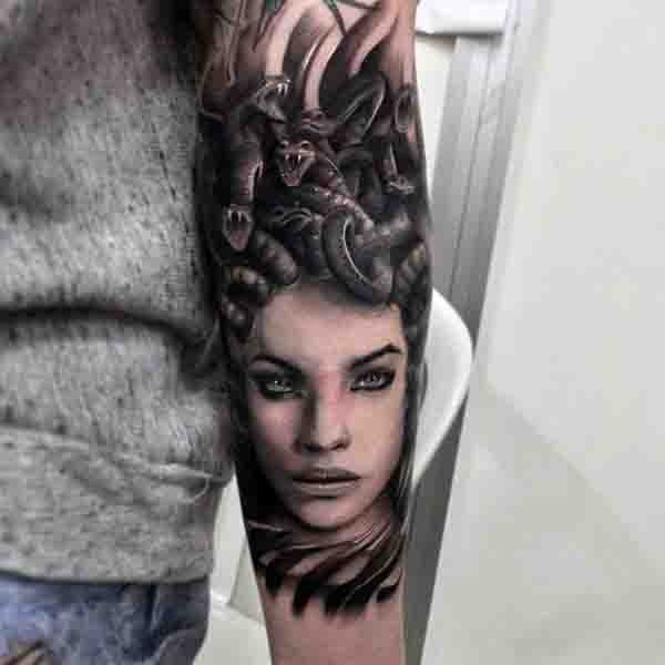 Natural looking black ink seductive Medusa head tattoo on arm
