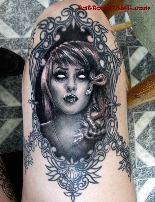 Natural looking coll painted detailed thigh tattoo of demonic Medusa portrait