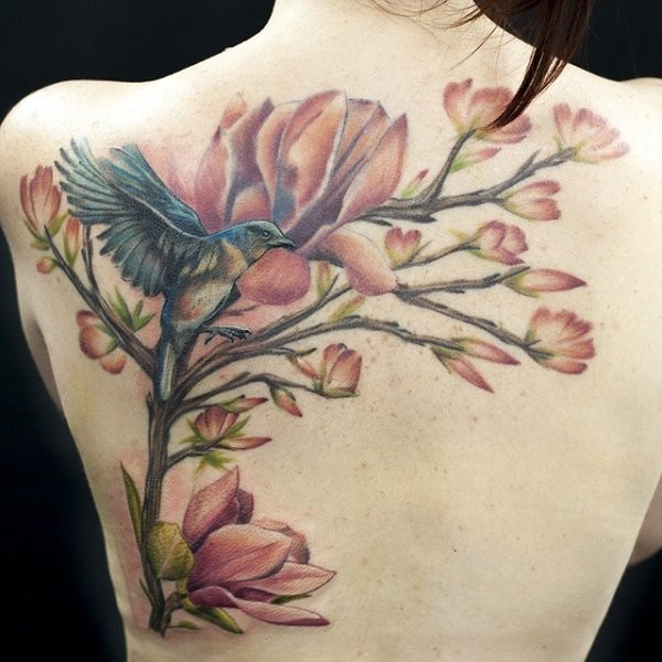 Natural looking colored back tattoo of tree branch with flowers and bird