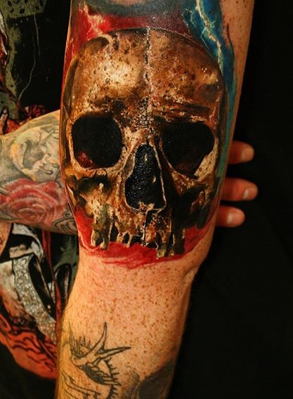 Natural looking colored biceps tattoo of human skull part