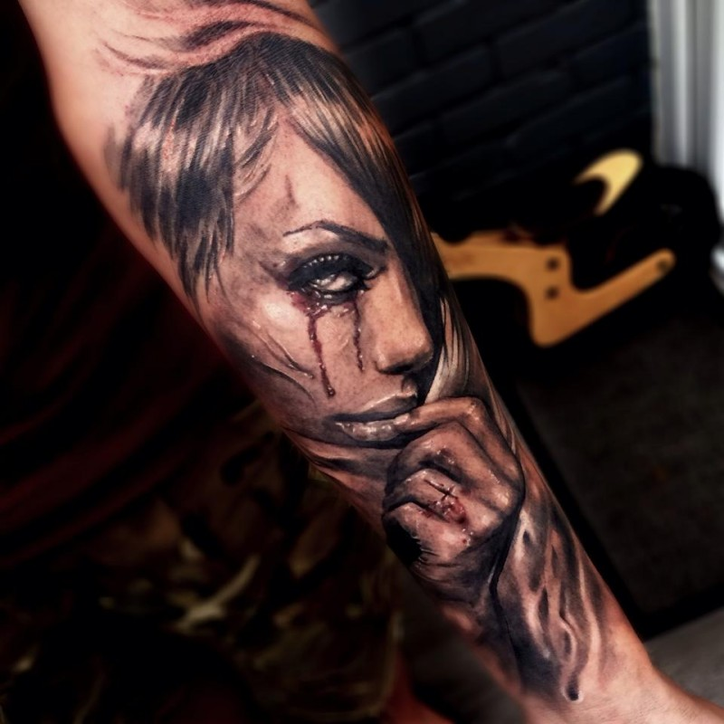 Natural looking colored forearm tattoo of crying woman with cross
