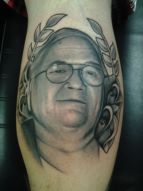 Natural looking colored man in glasses portrait tattoo on leg stylized with flowers and leaves