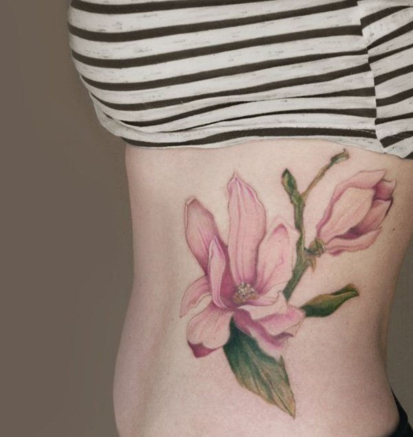Natural looking colored pink flowers tattoo on side