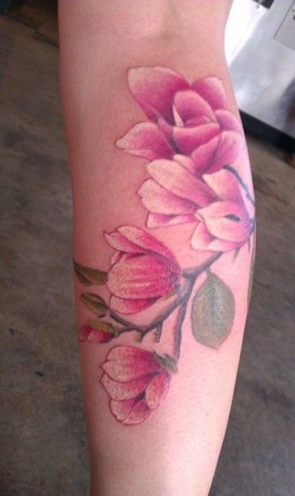 Natural looking colored pink flowers tattoo on leg