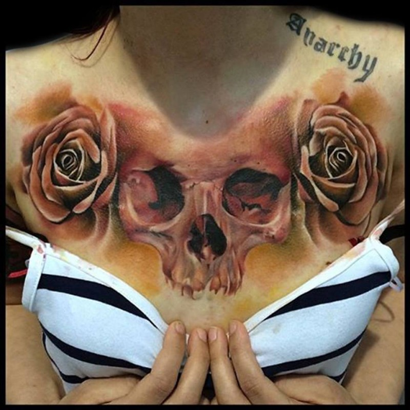 Natural looking colored rose flowers tattoo on chest with human skull