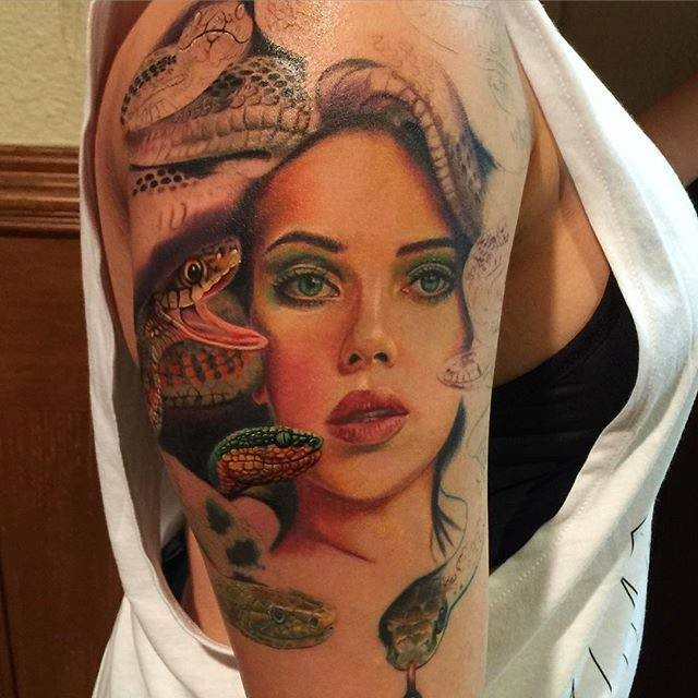 Natural looking colored shoulder tattoo of woman face with snakes