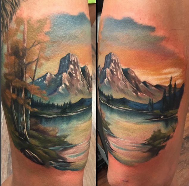 Natural looking colored tattoo fo beautiful mountains with lake