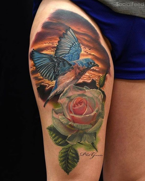 Natural looking colored thigh tattoo of beautiful bird with flowers